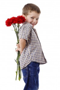 Smiling boy hiding a bouquet