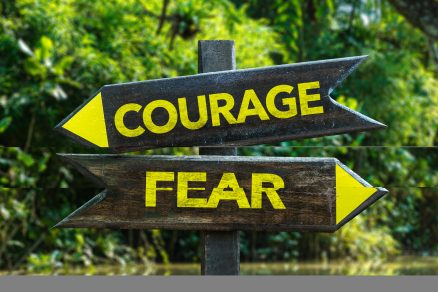 Courage - Fear signpost with forest background