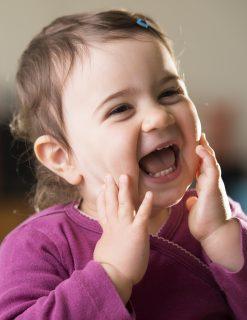 cute baby girl in purple looking aside laughing